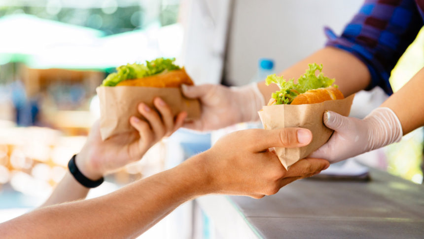 Close-up of male buying two hot dog in a food truck, outdoors