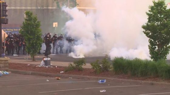 Protesters encountering law enforcement as tear gas is deployed