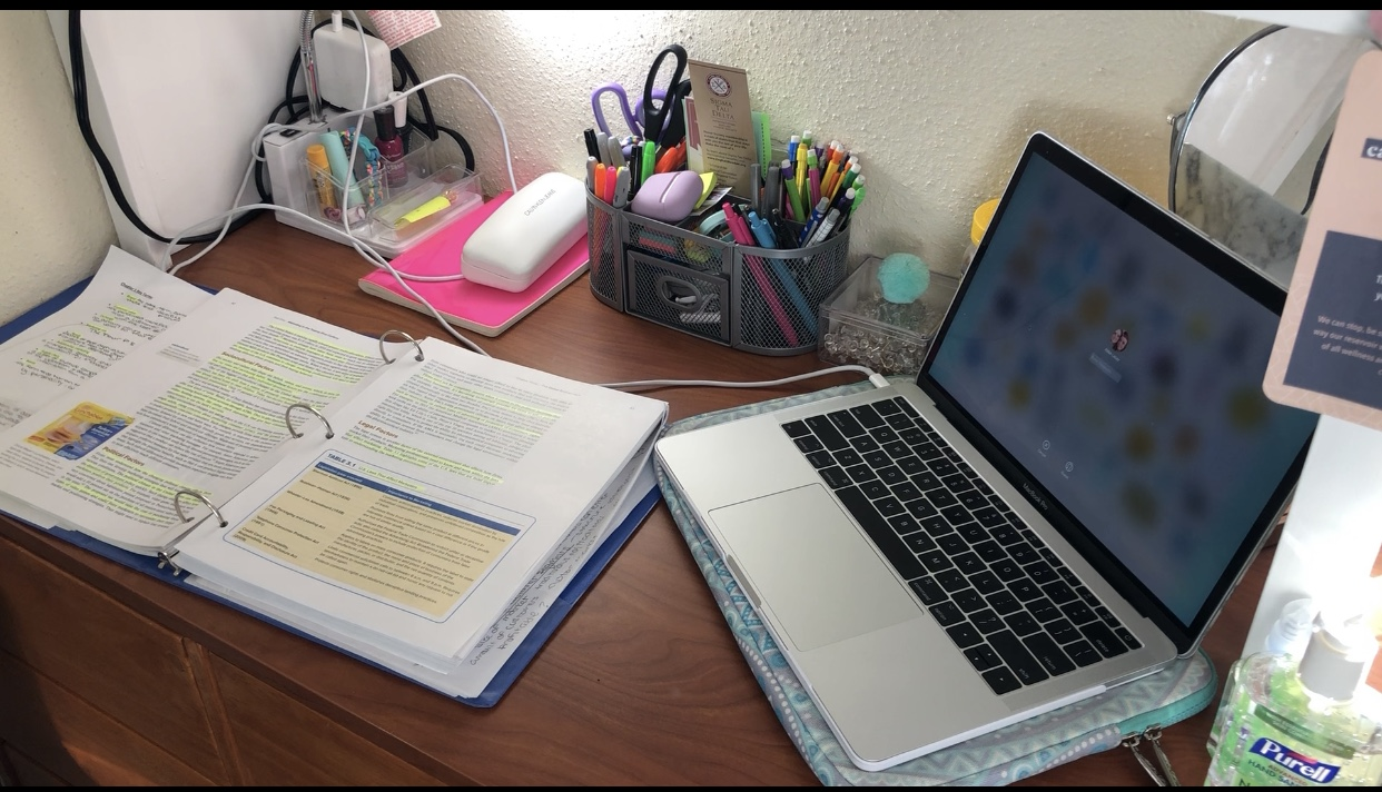 Laptop and textbook on a desk