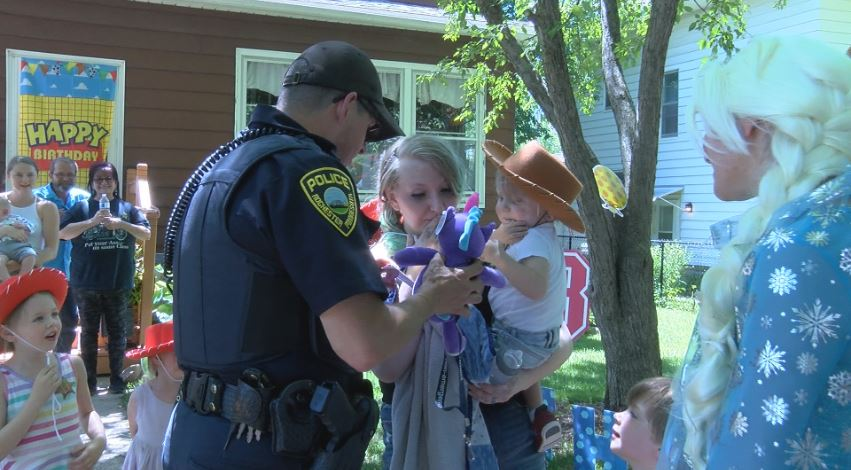 Rochtester Police Officer giving a stuffed animal to the birthday boy