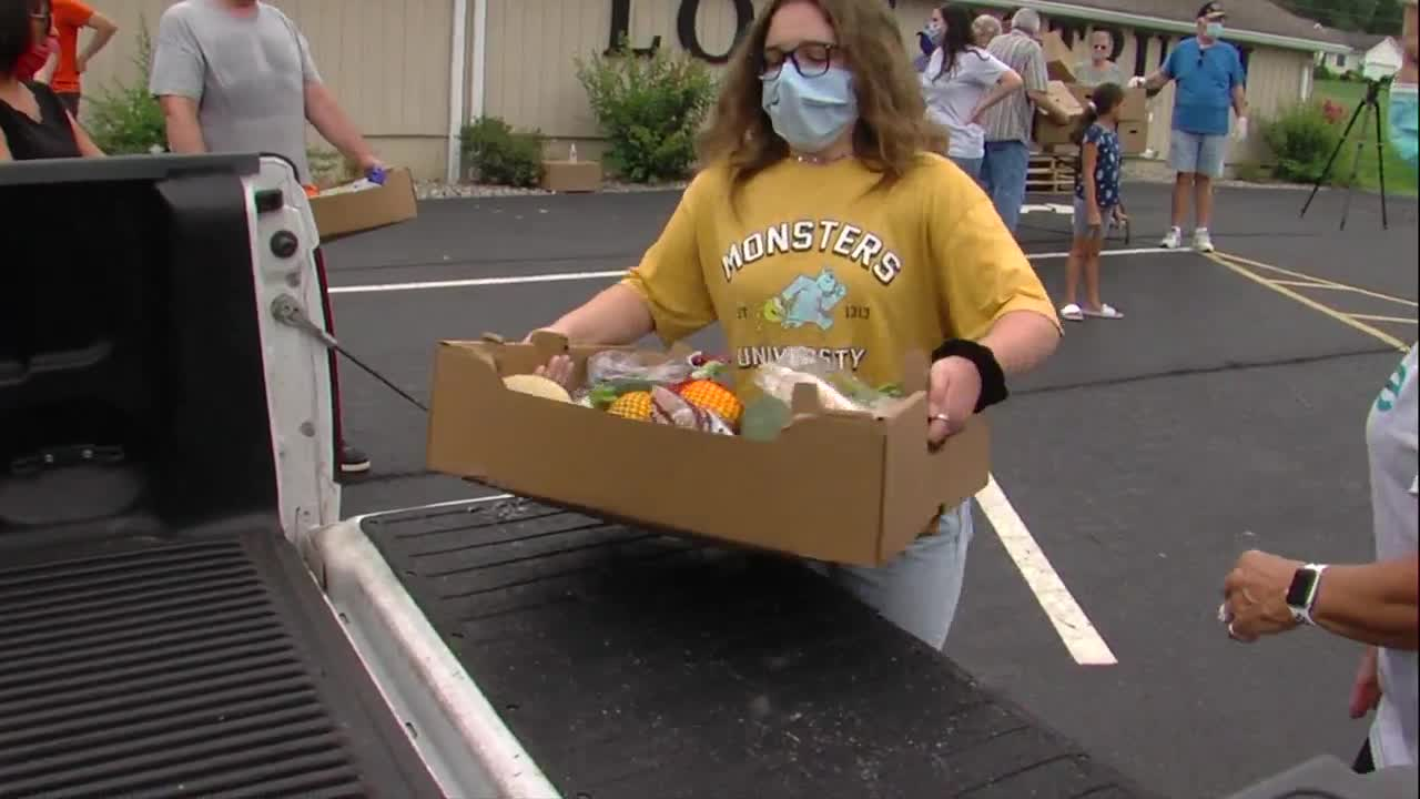 Box of fresh vegetables are carried to the bed of a truck waiting in a food-giveaway line.
