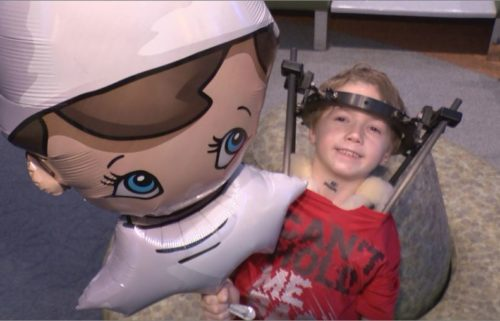 Child with an elf on the shelf balloon