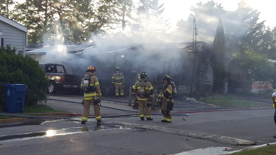 Firefighters in front of destroyed mobile home.