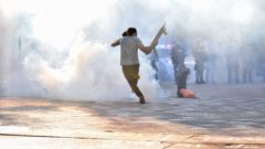 A protesters kicks tear gas back at police during unrest in downtown Madison. Roman Olivas/photo