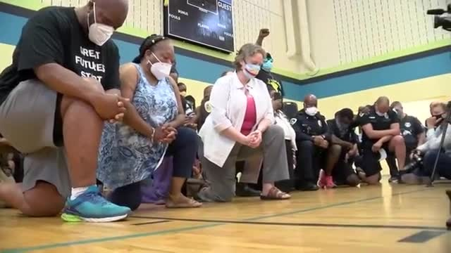 Community leaders take and knee to call for racial justice and an end to racism.