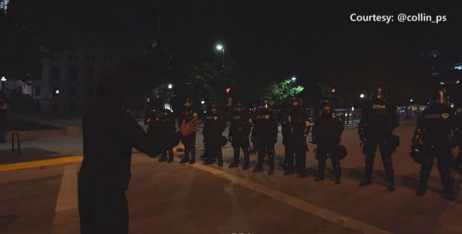 African American man addressed Madison police in riot gear.