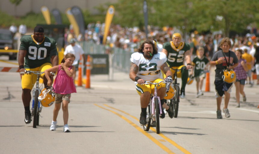 Packers players ride bikes to practice in 2010 to begin the season that would end in a Super Bowl victory.