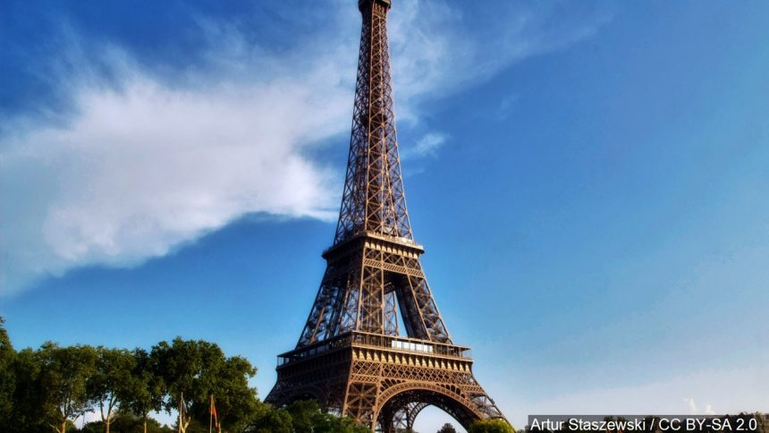 Eiffel Tower in Paris against a bright blue sky. The land mark is a popular destination when people travel Europe.